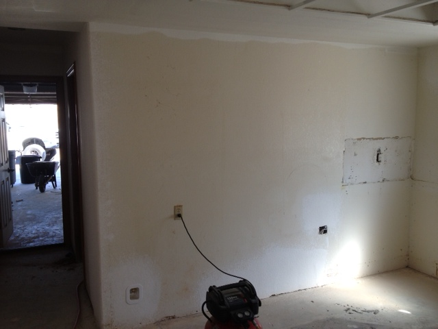 The shorter wall of this kitchen shows the electric outlet that's ready to accommodate the fridge.