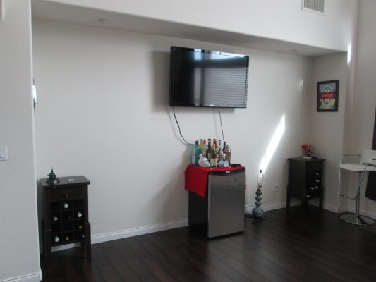 Three tiny wine cabinets and a cooler sit next to an empty wall...